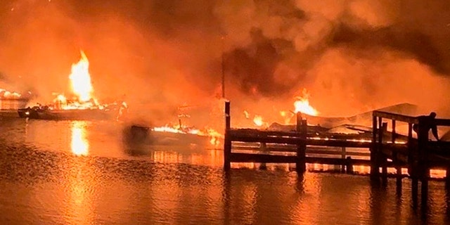 A fire burns on a dock where at least 35 vessels, many of them houseboats, were destroyed early Monday in Scottsboro, Ala. (AP/Jackson County Sentinel)