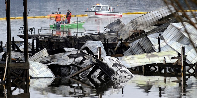People on boats patrol near the charred remains of a dock following a fatal fire at a Tennessee River marina in Scottsboro, Ala., on Monday. (AP)