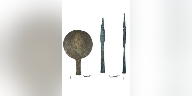Bronze mirror and iron spear heads from the burial.(Credit: Institute of Archaeology RAS)