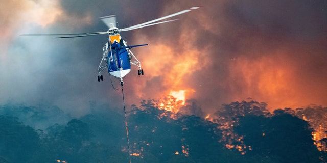 In this Monday, Dec. 30, 2019 photo provided by State Government of Victoria, a helicopter tackles a wildfire in East Gippsland, Victoria state, Australia.