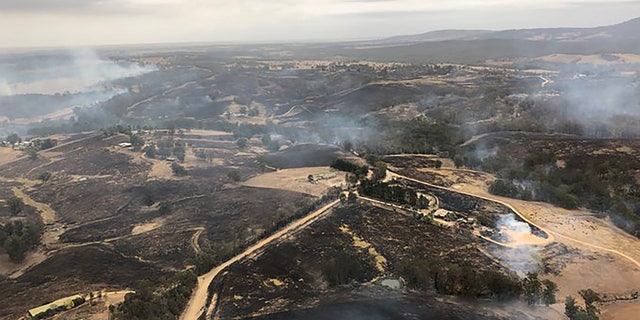In this Monday, Dec. 30, 2019, aerial photo, acres of scorched land are seen in Bairnsdale, Australia.