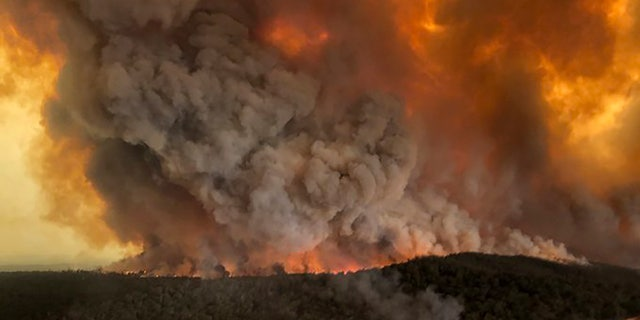 In this Monday, Dec. 30, 2019, aerial photo, wildfires rage under plumes of smoke in Bairnsdale, Australia.