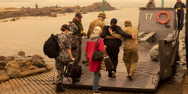 In this photo released by the Australian Department of Defense, evacuees board landing craft to be ferried out to the navy's HMAS Choules, Friday, Jan. 3, 2020, in Mallacoota, Victoria, Australia.