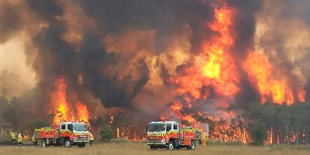 In this image dated Dec. 30, 2019, and provided by NSW Rural Fire Service via their twitter account, firefighters are seen as they try to protect homes around Charmhaven, New South Wales. (Twitter@NSWRFS via AP)