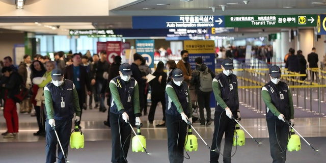 Workers spray antiseptic solution on the arrival lobby amid rising public concerns over the possible spread of a new coronavirus at Incheon International Airport in Incheon, South Korea.