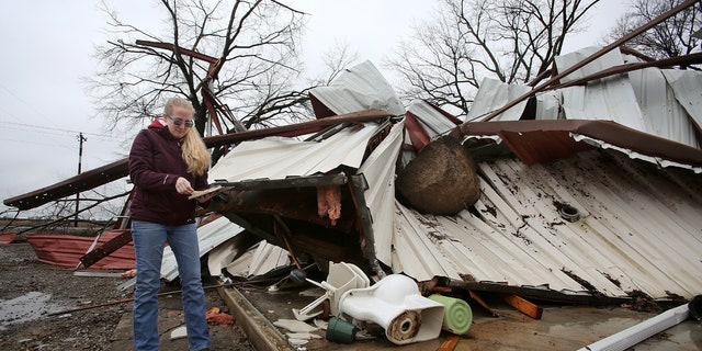 Scarlett Faulk looks at a Bible belonging to one of her brothers that she pulled out of from a destroyed building on her family's land on Saturday, Jan. 11, 2020, in southern Lonoke County, Ark.