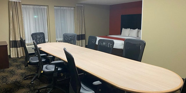 """The """"boardroom suite"""" came complete with a literalboardroom table and nine swivel chairs, as well as a queen-sized bed tucked into an alcove in the corner.<br>"""