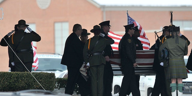 In this 2010 file photo, law enforcement officers carry the casket of Border Patrol officer and former U.S. Marine Brian Terry out of Greater Grace Temple after his funeral service in Detroit, Mich.