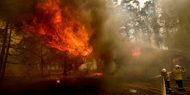 Firefighters battle the Morton Fire as it consumes a home near Bundanoon, New South Wales, Australia, Thursday, Jan. 23, 2020. (AP Photo (AP Photo/Noah Berger)