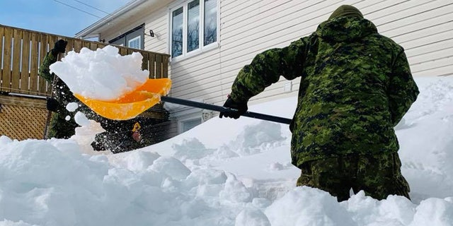Soldiers from the Canadian Armed Forces can be seen shoveling out a home on Monday.