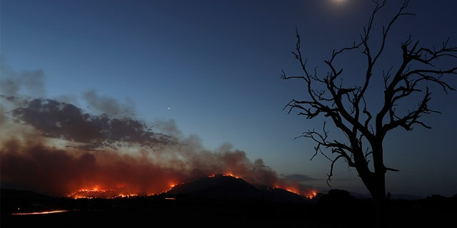 A wildfire threatening property glows at dusk near Clear Range, south of the Australian capital of Canberra on Friday.