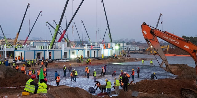 Construction workers labor at the site of the Huoshenshan temporary field hospital being built in Wuhan in central China's Hubei Province, on Jan. 30, 2020.