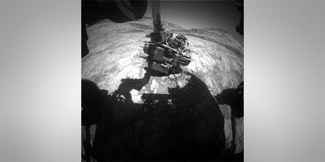 This Hazcam image shows Curiosity's arm extended out to perform an APXS analysis of the bedrock. Curiosity has to know the exact angle of every joint to move safely. (Credit: NASA/JPL-Caltech)