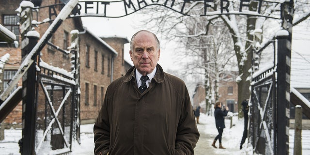 """President of the World Jewish Congress Ronald Lauder stands near the lettering """"Arbeit macht frei"""" (work makes you free) at the Auschwitz entrance gate in 2015 (ODD ANDERSEN/AFP via Getty Images)"""