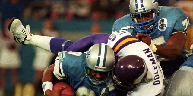 Detroit Lions Quarterback Rodney Pete (9) gets sacked by Minnesota Vikings Chris Doleman (56) as the Lions Lomas Brown (R) tries to help in the second quarter of their NFL game, 5 December 1993. (Photo byMICHAEL E. SAMOJEDEN/AFP via Getty Images)