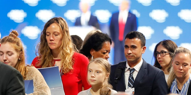 Swedish environmental activist Greta Thunberg, center, leaves as U.S. President Donald Trump, rear right, and Executive Chairman Klaus Schwab, rear left, are seen at the World Economic Forum in Davos, Switzerland, Tuesday, Jan. 21, 2020. The 50th annual meeting of the forum will take place in Davos from Jan. 21 until Jan. 24, 2020. (AP Photo/Markus Schreiber)