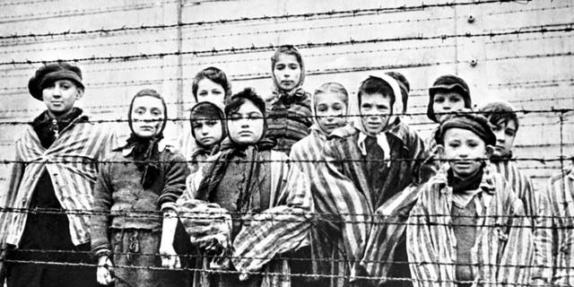 A group of child survivors behind a barbed-wire fence at the Nazi concentration camp at Auschwitz-Birkenau in southern Poland, on the day of the camp's liberation by the Red Army, 27th January 1945. Photo taken by Red Army photographer Captain Alexander Vorontsov during the making of a film about the liberation of the camp.