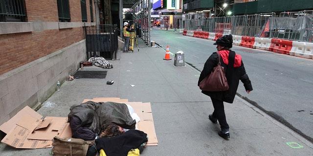 Homeless people sleep on a sidewalk in Manhattan in October 2019.
