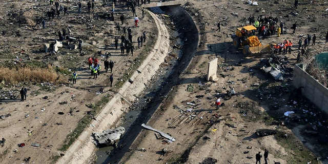 Rescue workers search the scene where a Ukrainian plane crashed in Shahedshahr, southwest of the Iranian capital of Tehran, on Wednesday.