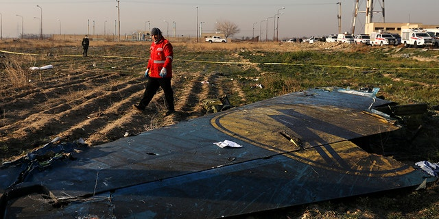 A rescue worker searches the scene where the Ukrainian plane crashed. It was heading for Kiev. (AP)