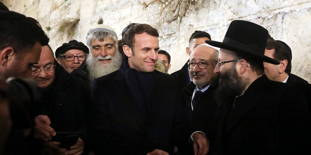 French President Emmanuel Macron, center, visits the Western wall, the holiest site where Jews can pray, in the Old City of Jerusalem, Wednesday, Jan. 22, 2020. Dozens of world leaders have descended upon Jerusalem for the largest-ever gathering focused on commemorating the Holocaust and combating modern-day anti-Semitism. (AP Photo/Mahmoud Illean)