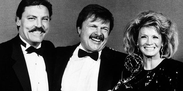 "FILE - This Sept. 21, 1986 file photo shows actor John Karlen, center, who portrays the husband of detective Mary Beth Lacey on the TV show ""Cagney & Lacey, "" posing with presenters Stacy Keach, left, and Angie Dickinson after Karlen won an Emmy for best supporting actor at the Emmy Awards in Pasadena, Calif."