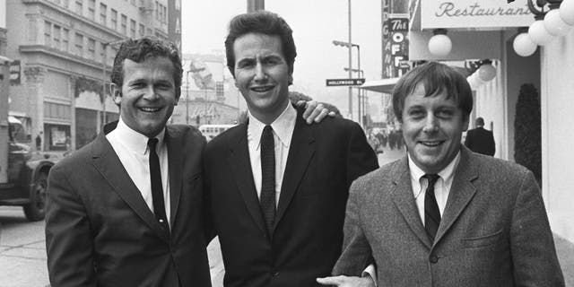 """In this Jan. 31, 1967, file photo, members of the Kingston Trio, from left: Bob Shane, John Stewart and Nick Reynolds are pictured in the Hollywood section of Los Angeles. Shane, the last surviving original member of the popular folk group the Kingston Trio and the lead singer on its million-selling ballad """"Tom Dooley"""" and many other hits, died Sunday, Jan. 26, 2020, in Phoenix. He was 85."""