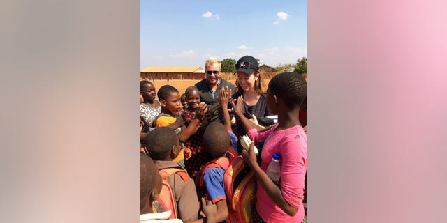 White House staffer Carolina Hurley greeting a group of schoolchildren during her visit to the Chipala Primary School in Lilongwe, Malawi.