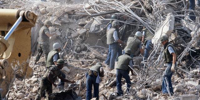 Морские пехотинцы США разыскивают выживших и тела в обломках - все, что осталось от их казарм в Бейруте - после того, как в 1983 году в здание взорвалась бомба-самоубийца, взорвавшая 241 военнослужащих США и ранившая более 60 человек.