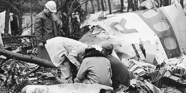 Five rescue workers search the wreckage of a plane crash in Huntington, West Virginia. The plane carried the entire Marshall University Football team and all passengers were killed.