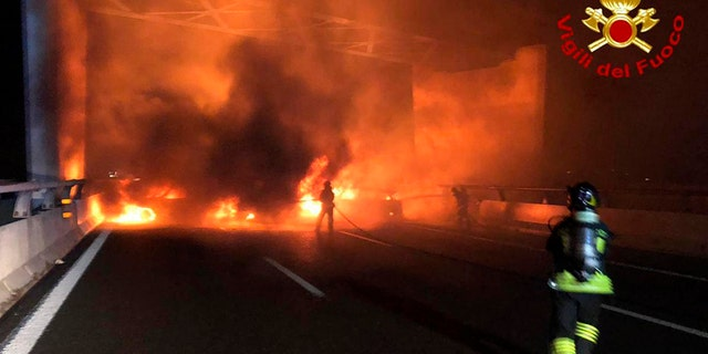 In a bid to rob an armored vehicle, a gang of thieves set up barriers of burning vehicles and spilled nails on a highway near Milan but were foiled when the driver evaded their traps. (AP/Italian Firefighters)