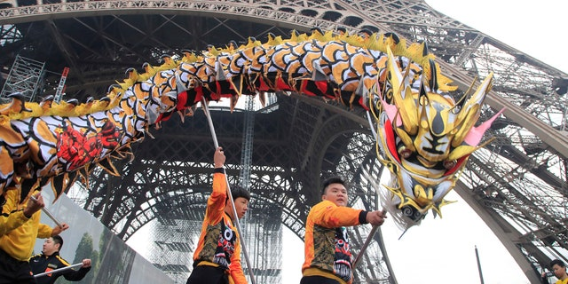 Members of the Chinese community dance with costumes to mark the Chinese New Year at the Eiffel Tower in Paris, Saturday Jan. 25, 2020.