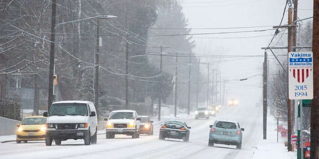 Vehicles travel through the snow on Tieton Drive on Wednesday, Jan. 15, 2020, in Yakima, Wash.
