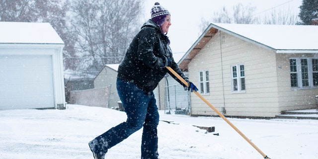 Ashley Reilly sweeps snow from her neighbor's driveway on Wednesday, Jan. 15, in Yakima, Wash.