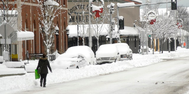 A pedestrian makes her way along a snow-covered Front Street in downtown Port Angeles, Wash., on Wednesday, Jan. 15, 2020, after heavy snow blanketed the city overnight.