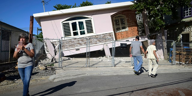 Residents surveyed damage where a home partially collapsed in Guanica on Monday. (AP Photo/Carlos Giusti)