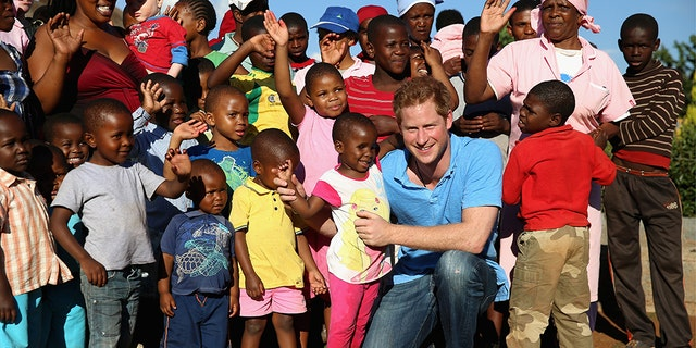 Prince Harry plays with a three year old blind girl named Karabo during a visit to Phelisanong Children's Home on Dec. 6, 2014 in Pitseng, Lesotho.