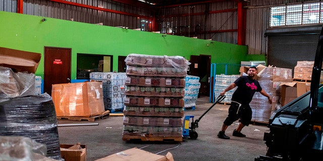 A man pulls a pallet of gas canisters believed to have been from when Hurricane Maria struck the island in 2017 in a warehouse in Ponce, Puerto Rico on Jan. 18, 2020, after a powerful earthquake hit the island. (Photo by Ricardo ARDUENGO / AFP)
