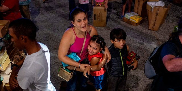 A girl cries next to her mother after police evacuated people breaking into a warehouse filled with supplies, believed to have been from when Hurricane Maria struck the island in 2017 in Ponce, Puerto Rico on Jan. 18, 2020, after a powerful earthquake hit the island. (Photo by Ricardo ARDUENGO / AFP)