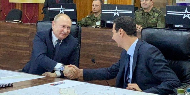 Russian President Vladimir Putin, center, meets with Syrian President Bashar Assad, right, in Damascus, Syria, on Tuesday, Jan. 7, 2020. Putin's visit was the second to the war-torn country where his troops have been fighting alongside Syrian government forces since 2015. (Syrian Presidency via AP)