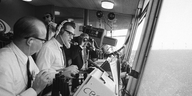 The first Super Bowl was played at the Memorial Coliseum in Los Angeles, Jan. 15, 1967.In foreground is announcer Ray Scott. Wearing headset is commentator Frank Gifford. In the background, holding binoculars, is Jack Whitaker. (Photo by CBS via Getty Images)