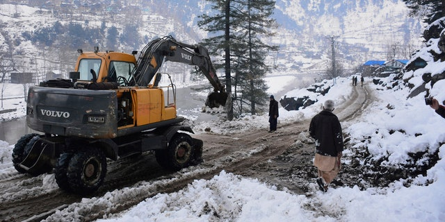 Workers with heavy machinery clear a snow-covered road in Keran, a small town in Neelum Valley, Pakistan-administered Kashmir, Tuesday, Jan. 14, 2020.