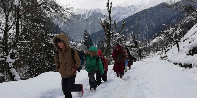Kashmiri children walk through snow-covered road after heavy snowfall in Neelum Valley, Pakistan-administered Kashmir, Wednesday, Jan. 15, 2020.