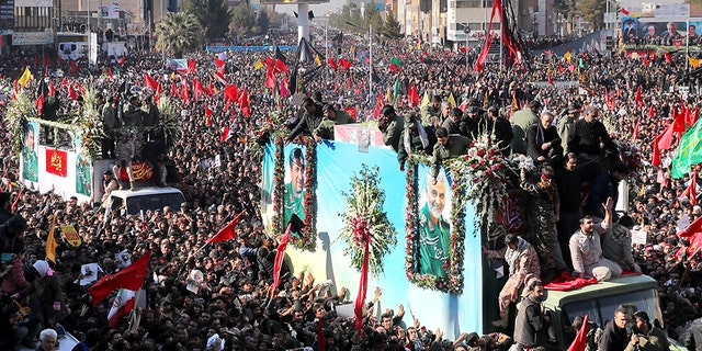 Coffins of Gen. Qassem Soleimani and others who were killed in Iraq by a U.S. drone strike, are carried on a truck surrounded by mourners during a funeral procession, in the city of Kerman, Iran, on Tuesday.