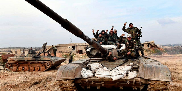 Syrian army soldiers flash the victory sign as they stand on their tank in western rural Aleppo, Syria, on Monday. (AP/SANA)
