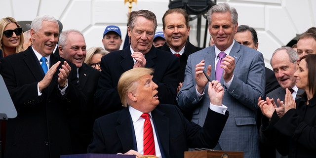 President Trump hands out pens after signing a new North American trade agreement with Canada and Mexico, during an event at the White House, Wednesday, Jan. 29, 2020, in Washington. (Associated Press)