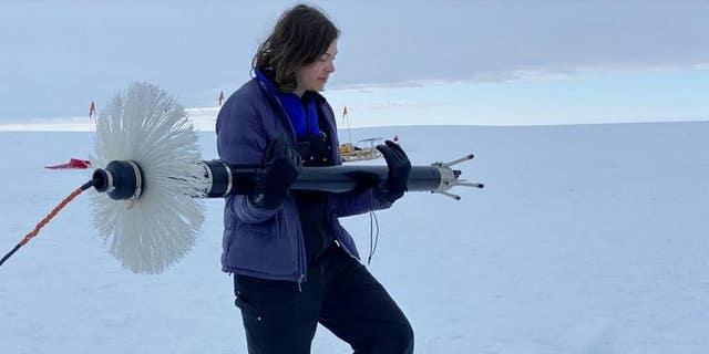 NYU graduate student Aurora Basinski carries a turbulence measuring device to the borehole on Thwaites Glacier. (David Holland, NYU and NYU Abu Dhabi)