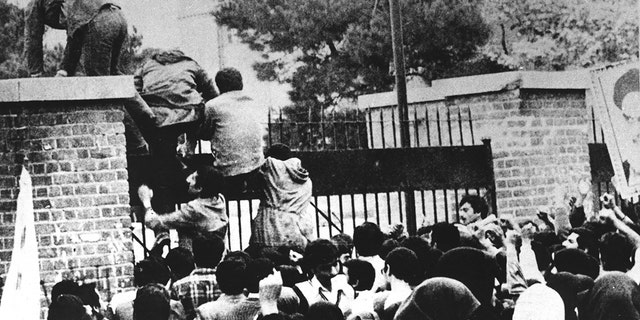 Иранские студенты перелезают через стену посольства США в Тегеране в ноябре 1979 года.