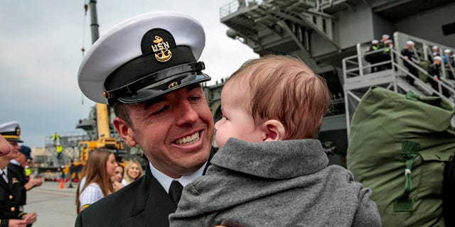 New dad Chief Mass Communication Specialist Mike Lenart holds his child for the first time after the USS Abraham Lincoln came home Monday.