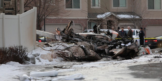 Firefighters and other investigators look at the debris from a small private plane that crashed in a residential area Wednesday, in Roy, Utah. The small plane crashed, killing the pilot as the aircraft narrowly avoided hitting any townhomes, authorities said. (Ben Dorger/Standard-Examiner via AP)